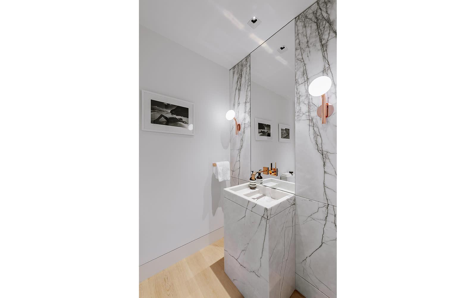 powder room with decorative rose gold scones inside a los angeles condominium